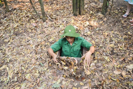 Ho Chi Minh City, Vietnam - Mar 8, 2013 : Tour Guide demonstrating how a Vietcong hide into the Cu Chi Tunnels Editöryel