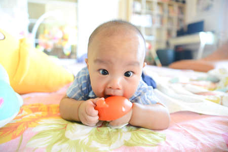 Cute little Asian baby boy chewing teething, Baby first toy