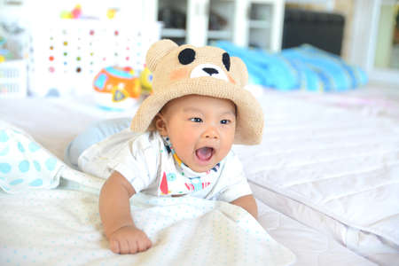 Cute little Asian baby boy wearing hand-made hat smiling at camera