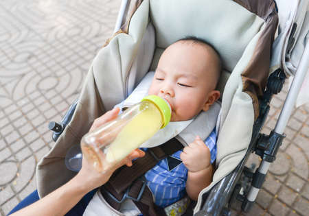 Cute little Asian baby on a stroller sucking milk from bottle in the park