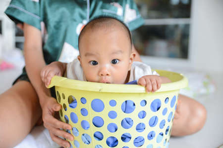 Cute little Asian baby hiding in bucket