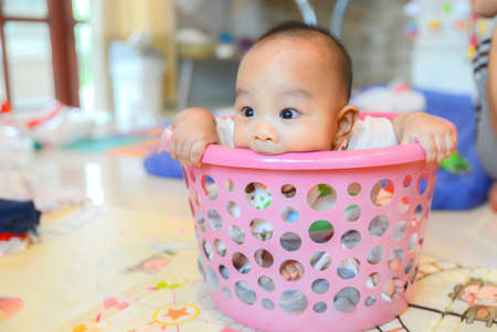 Cute Asian baby boy hiding in bucket