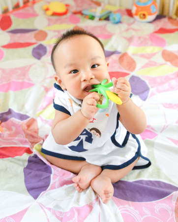 Cute Asian little baby boy chewing teething, Baby first toy