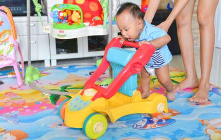 Asiatischer Babyjunge, der Lauflernhilfe, Babyspielzeug spielt