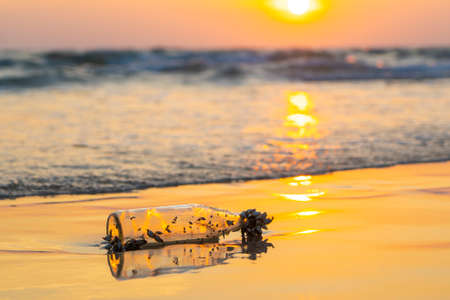 Old Glass Bottle Lies On Beach at Sunset Stockfoto