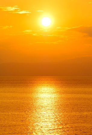 Image shows a setting sun over the ocean
