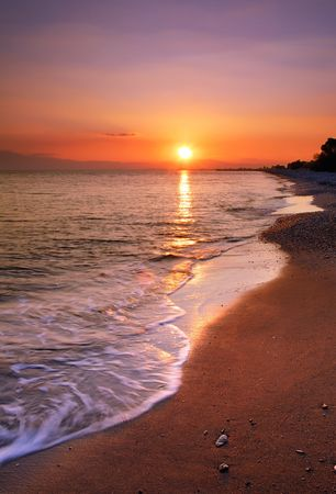 image shows a deserted beach at sunset photo