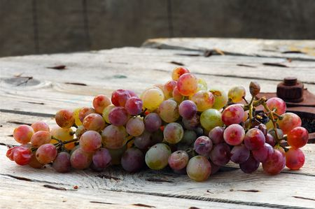 Image shows a bunch of grapes on a wooden table