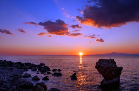 Image shows a sunset over the Messinian bay, Greece, with a rocky seascape in the foreground