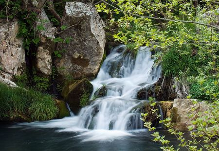 Image shows a small waterfall in a European forest