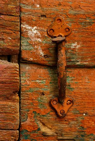 Image shows a rusty handle on a highly textured country door