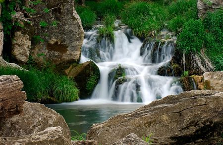 Image shows a small waterfall in a rocky landscape