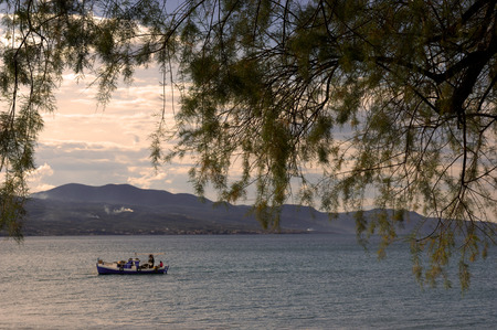 Image shows a fishing boat framed by a tree in the foreground photo