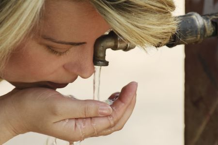 Caucassian young woman drinking water from a tap Stock Photo