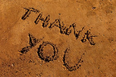 Image shows a thank you message written on wet sand photo