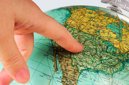Image shows an old  terrestrial globe with a finger pointing at the United States