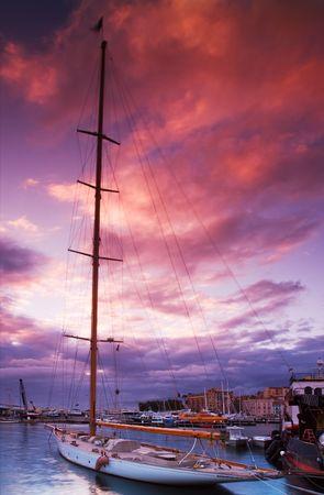 jachthaven: Beeld toont een afgemeerde zeilboot onder een dramatische zonsondergang hemel. Beeld vastgelegd in Cannes, Frankrijk
