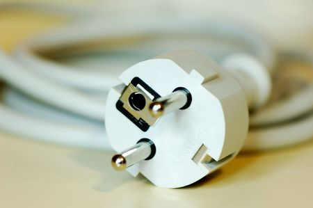 Close-up shot of a european plug connected to a long cable and photographed with shallow depth of field