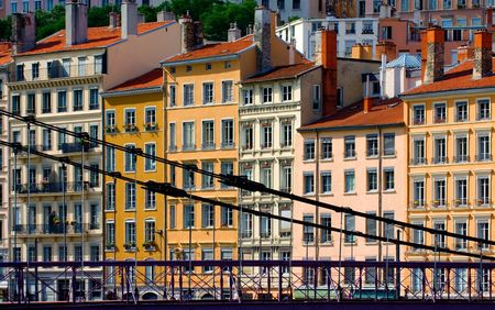 Image shows a series of colorful buildings in the city of Lyon, France, washed in the warm afternoon sunlight. One of the famous Lyon hanging bridges is seen in the foreground.