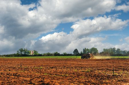 Image of a tractor working on a semi-plowed field
