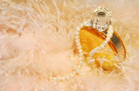Picture of a perfume bottle with a pearls necklace around it, sitting among feathers from a womans wardrobe. Room for text