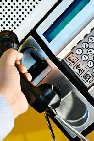 make public: Picture of a male hand retrieving the handset of a public telephone in order to make a call Stock Photo