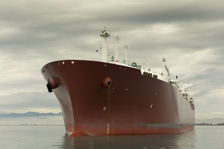 Large red liquefied gas carrier ship anchored near the shore Stock Photo