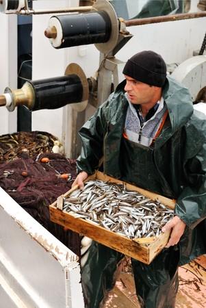 pescador: Joven pescador, en tiempo lluvioso, con una caja de madera llena de peces peque�os. Foto de archivo