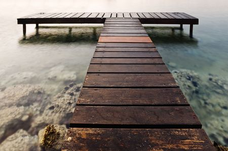 A T-shaped wooden pier photographed in the early hours of the morning