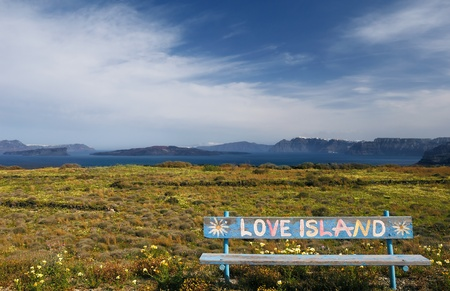 """Spring setting on the island of Santorini with a bench bearing the text """"Love Island"""" photo"""