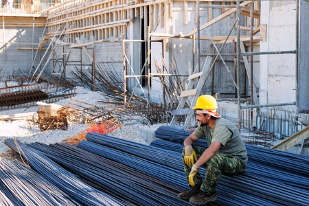 job site: Construction worker resting on piles of reinforcement steel bars, in a busy construction site