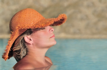 Young beautiful woman in a straw hat enjoying the sun in the pool Stock Photo - 9345078