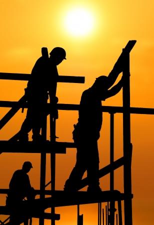 trabajadores: Silueta de trabajadores de la construcci�n en andamio trabajando bajo un ardiente sol Foto de archivo
