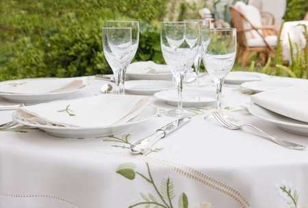 Table setting for garden banquet with expensive table cloth, silverware, and wine glasses Stock Photo - 9412305