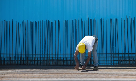 Authentic construction worker installing binding wires to reinforcement steel bars in front of a blue insulated surface prior to cement pouring Stock Photo - 9596531