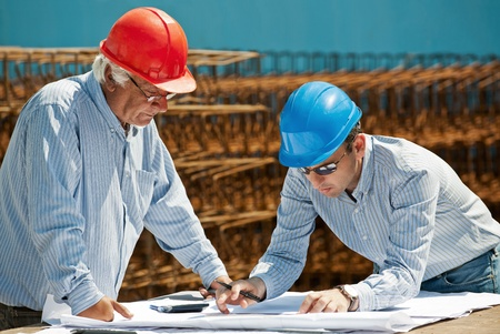 Young engineer shows a senior foreman the next steps in a construction project. Authentic professionals and site Stock Photo - 9596530