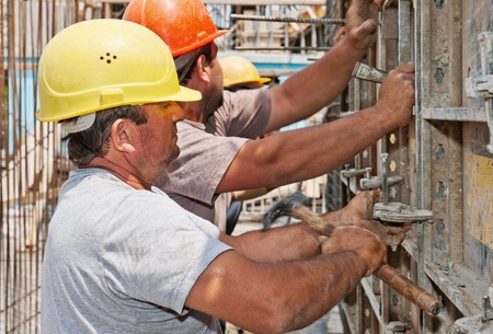 helmet construction: Authentic construction workers positioning cement formwork frames in place Stock Photo