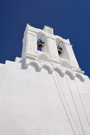 Belfry of an Orthodox church on the Greek Aegean island of Sifnos, against a blue sky Stock Photo