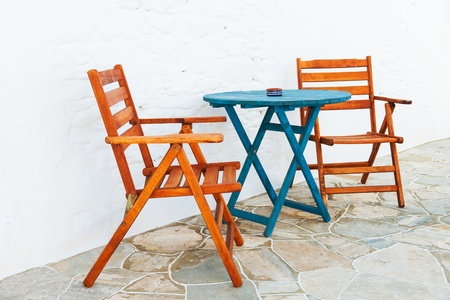 Colorful wooden chair and table arrangement from a Greek island alleyway