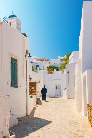 Greek Orthodox priest walking in an alleyway on the island of Sifnos Standard-Bild