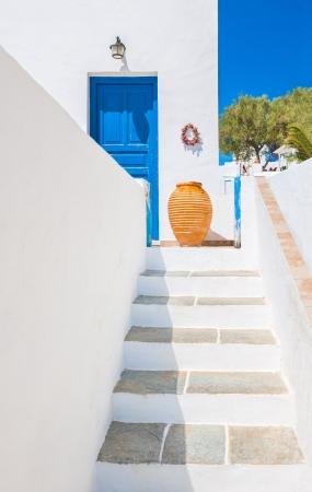 greek pot: Scala che porta a un ingresso con vaso di ceramica dalla bellissima isola di Sifnos, Grecia