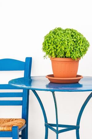 cycladic: Isola greca scena con il blu sedia, tavolo e vaso di fiori di basilico