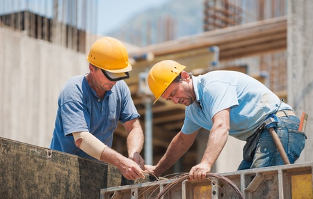 Authentic construction workers collaborating in the installation of cement formwork frames Stock Photo - 15482775