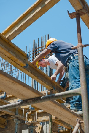 helmet construction: Authentic construction workers placing slab formwork beams in construction site Stock Photo