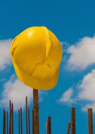 Construction protective helmet left hanging from reinforcement steel bars Standard-Bild