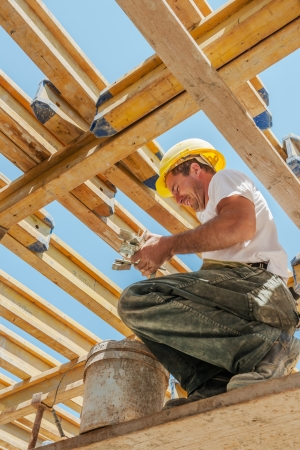 Smiling authentic construction builder working with clamps underneath slab formwork beams Stock Photo - 15747647