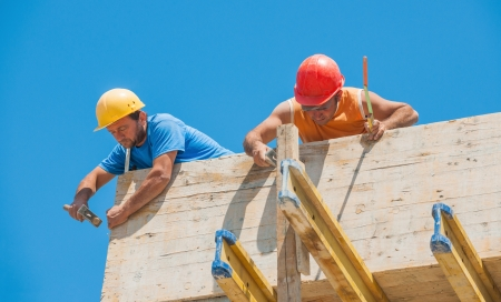Authentic construction builders working together for nailing wooden cement formwork in place Standard-Bild