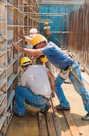 skilled: Authentic construction builders working together for positioning concrete formwork frames in place