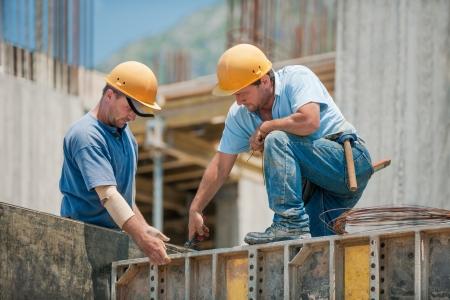 the job site: Due operai edili autentici che collaborano l'installazione di telai per casseforme di cemento Archivio Fotografico