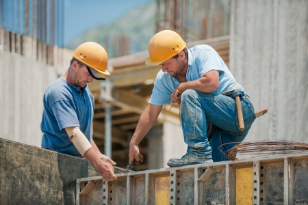 dělník: Dva autentické stavební dělníci spolupracující při instalaci betonových bednících rámů